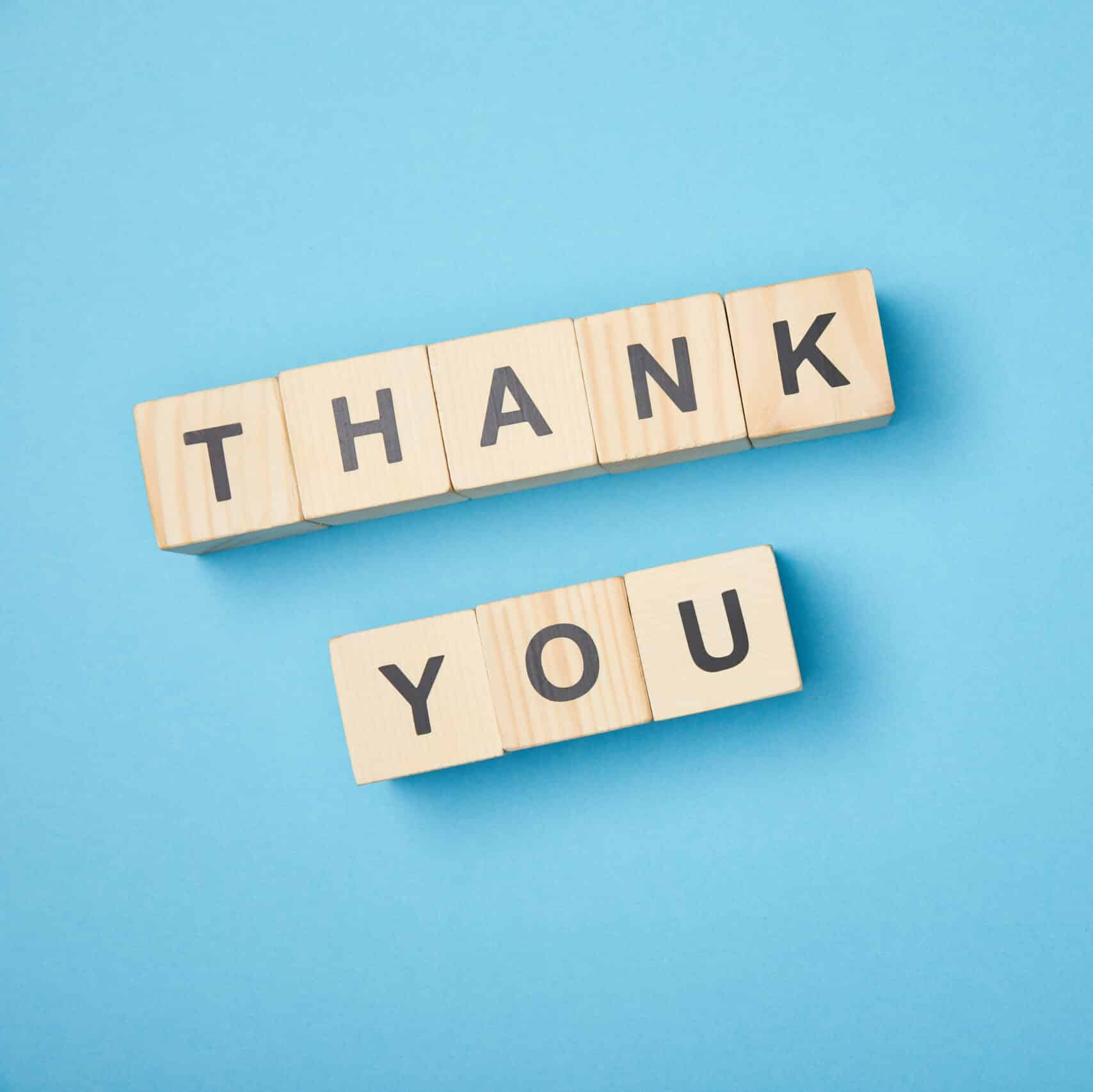 Top View Of Wooden Cubes With Thank You Words On Blue Background